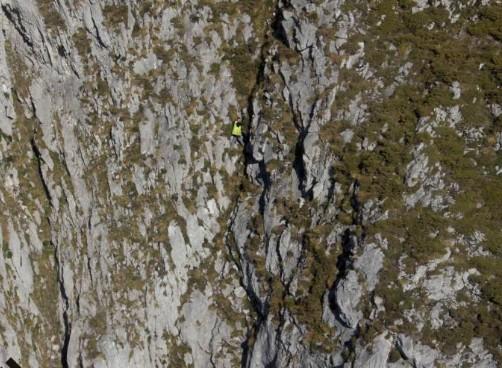 El cazador, de amarillo, en el centro de la imagen, en la zona donde quedó atrapado en Peñarredonda. / SEPA