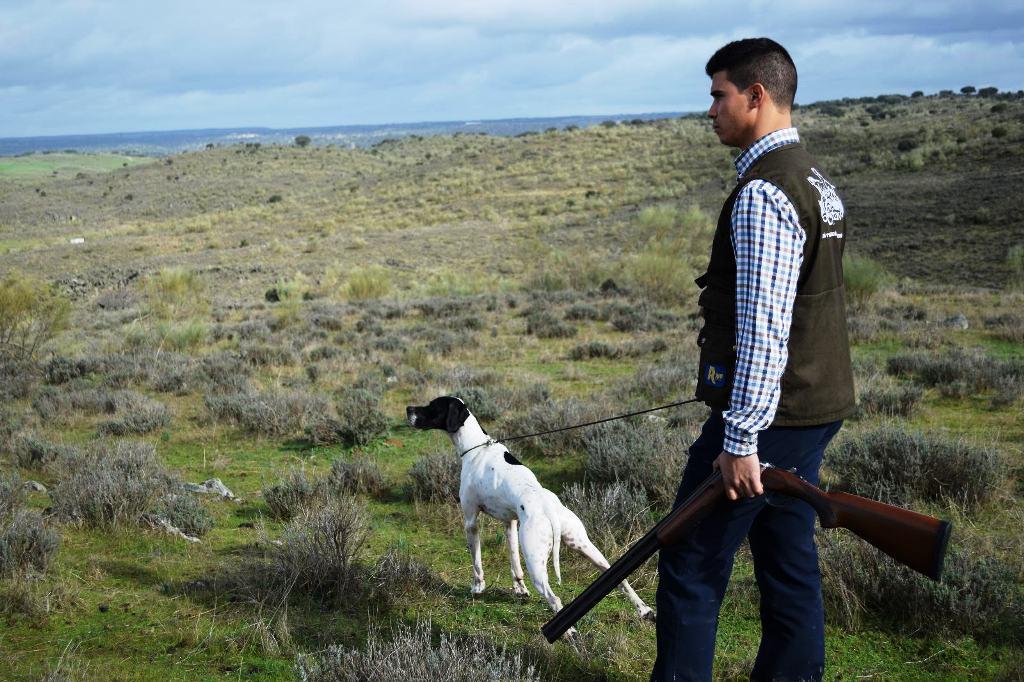 cazador con perro pointer y escopeta