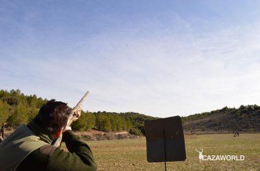 Un cazador apuntando a una perdiz en una suelta de perdices.