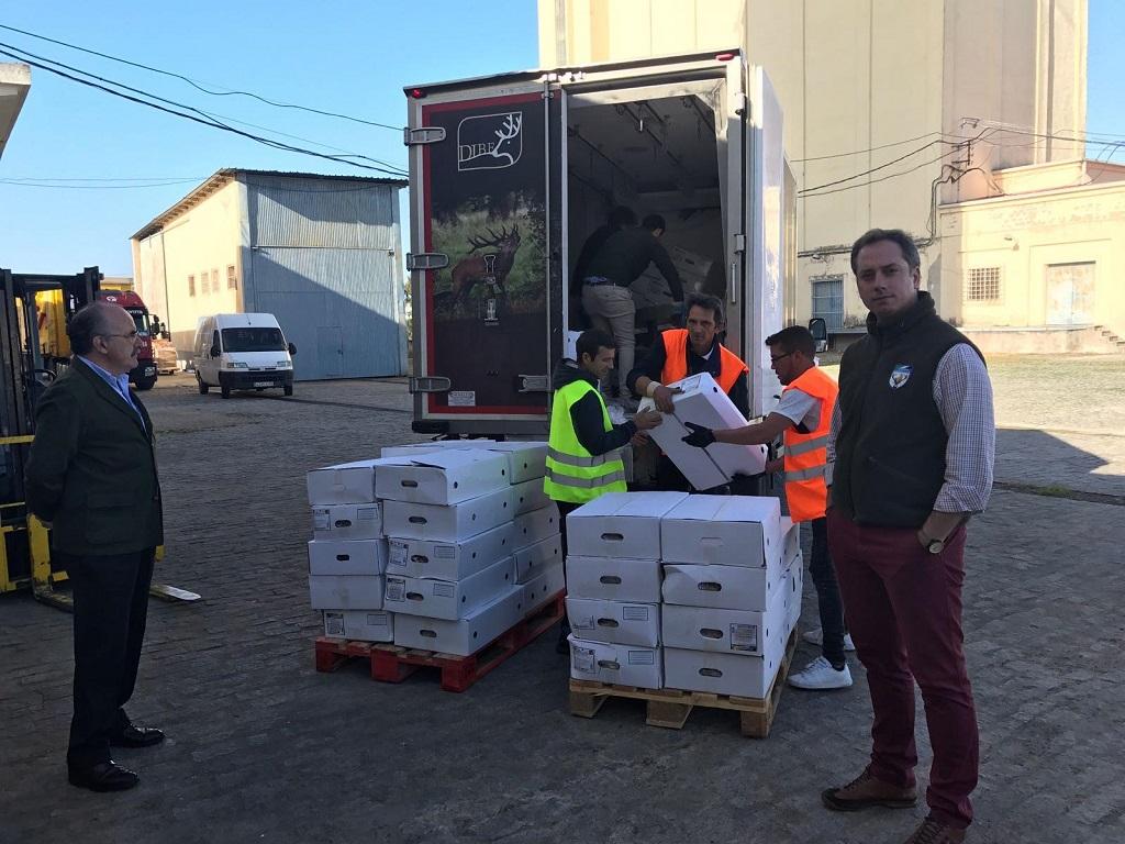 Momento en el que se descarga la carne de caza donada al Banco de Alimentos de Badajoz. Representantes de la Federación Extremeña de Caza y Cárnicas Dibe.