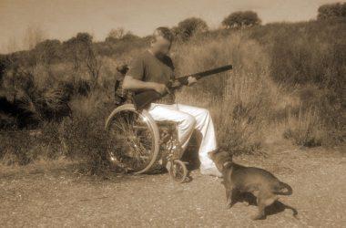 Cazador en silla de ruedas con perro