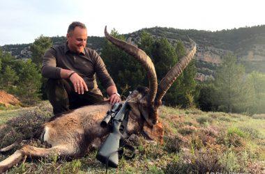 Un cazador posa con el macho montés cobrado tras un rececho en Teruel