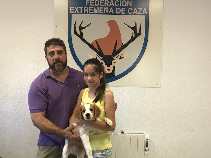 Carlos Tiburcio hace entrega de un cachorro de bretón con pedigree a la alumna ganadora.