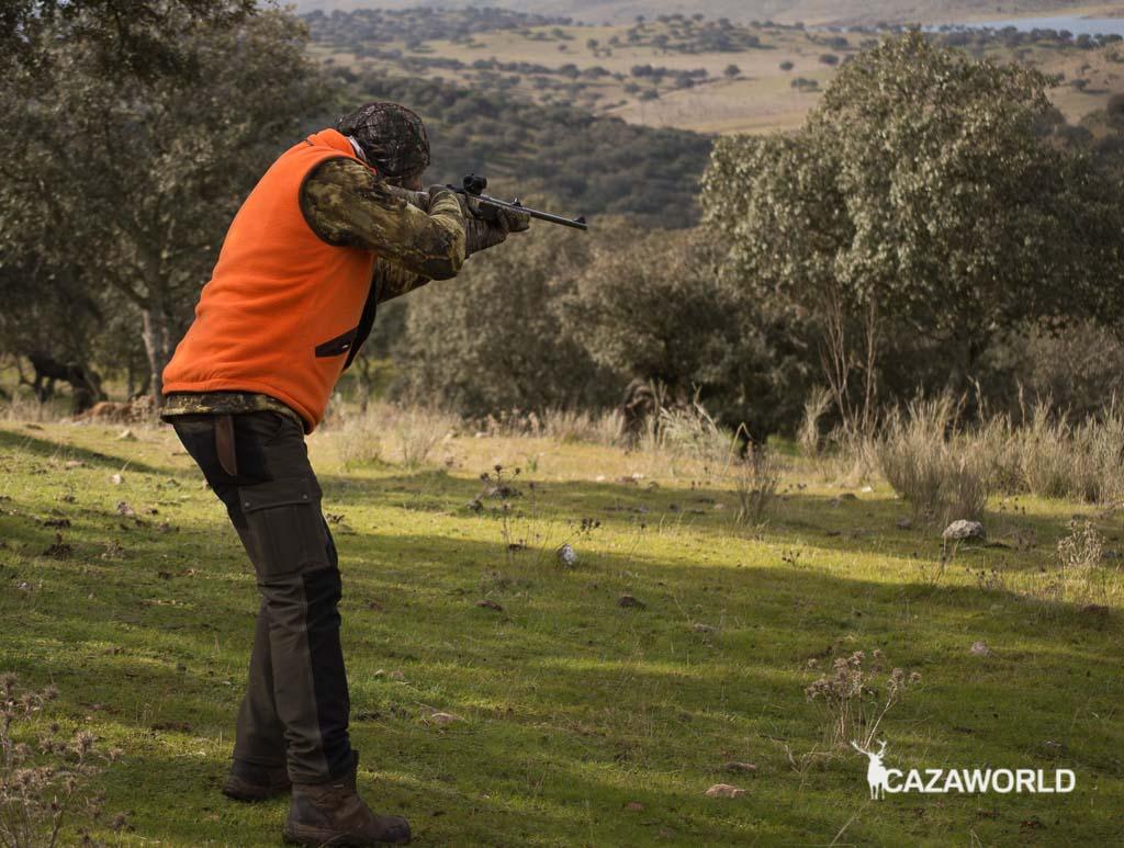 Un montero apunta y dispara con un rifle de cerrojo camo y un punto rojo.