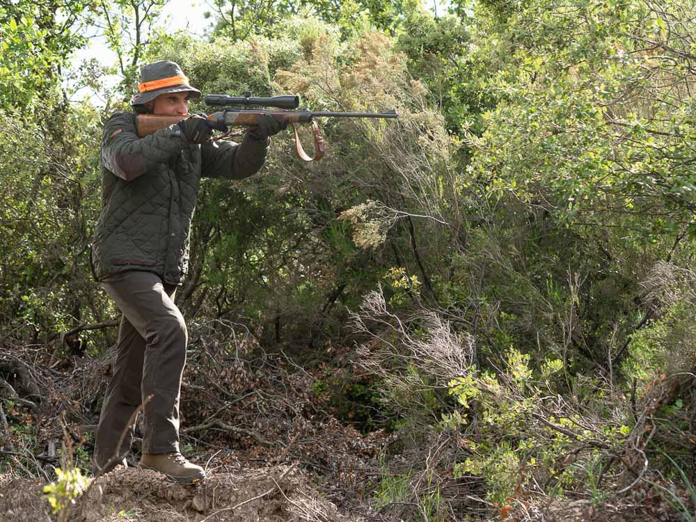 Cazador equipado con ropa Chiruca y la cazadora Padua apunta con su rifle de caza.