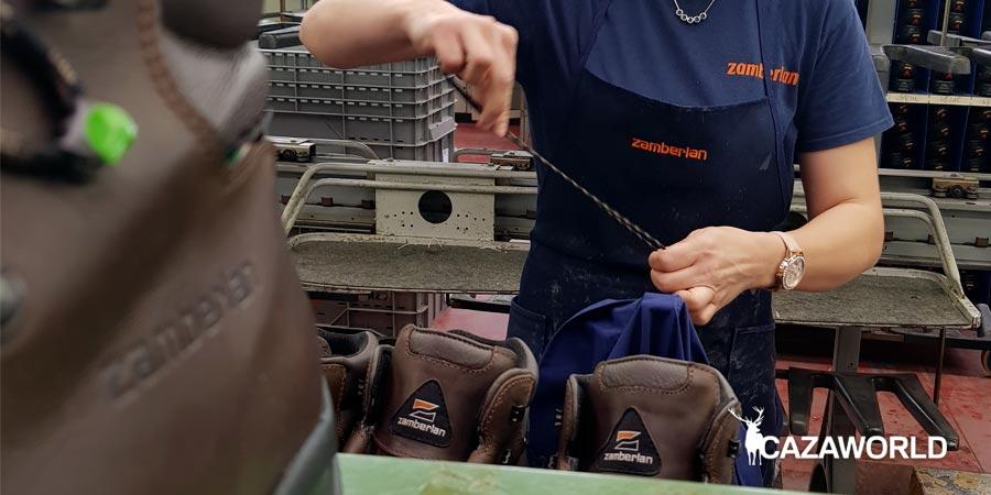 Una operaria se encarga de poner los cordones de las botas Zamberlan