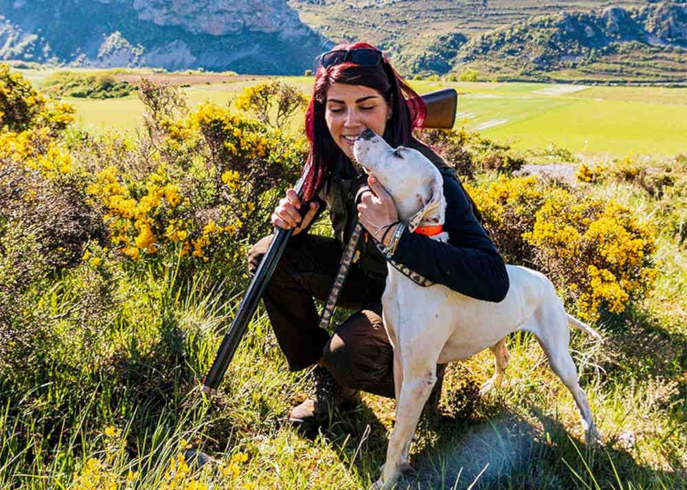 Imagen de una cazadora con su perro de caza